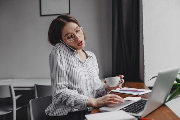 Pracownik Biurowy Zajęty Rozmawia Przez Telefon I Pracuje W Laptopie, Trzymając Filiżankę Herbaty. Darmowe Zdjęcia