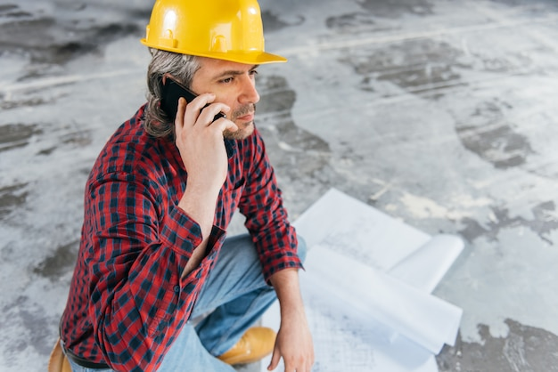 Pracownik budowlany sprawdza niebieskie odbitki i rozmawia przez telefon Premium Zdjęcia