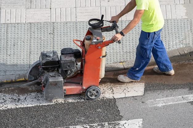 Pracownik Budowlany Tnący Betonową Podłogę Z Diamentową Piłą Tarczową Na Chodniku Premium Zdjęcia