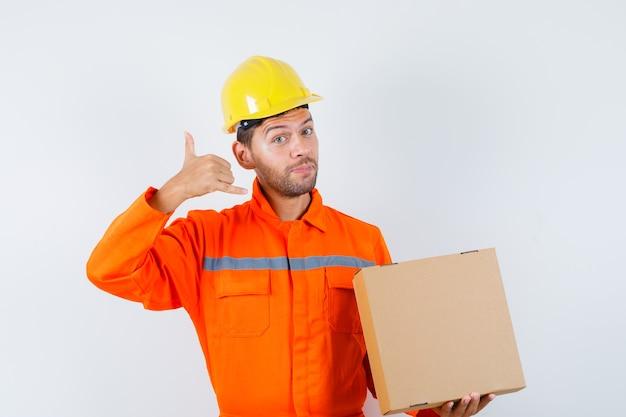 Pracownik Budowlany Trzymając Karton, Pokazując Gest Telefonu W Mundurze, Kasku I Delikatnie Patrząc. Przedni Widok. Darmowe Zdjęcia