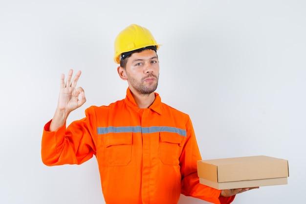Pracownik Budowlany Trzymając Karton, Pokazując Znak Ok W Mundurze, Widok Z Przodu Hełmu. Darmowe Zdjęcia