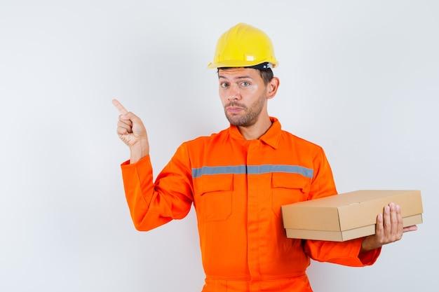 Pracownik Budowlany Trzymając Karton, Wskazując Na Lewy Róg W Mundurze, Widok Z Przodu Hełmu. Darmowe Zdjęcia