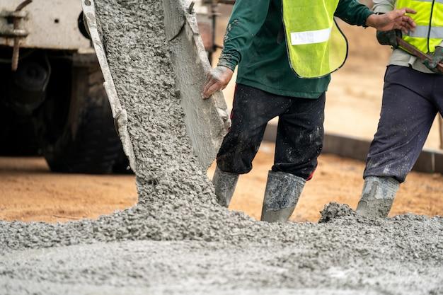 Pracownik budowlany wylewa mokry beton na budowie drogi Premium Zdjęcia