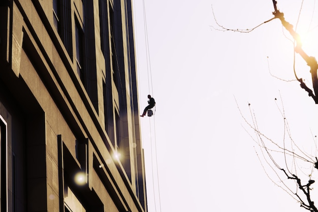 Pracownik Czyszczenia Usługi Okna Na Zewnątrz W Budynku Wysokim Wzrostem Premium Zdjęcia