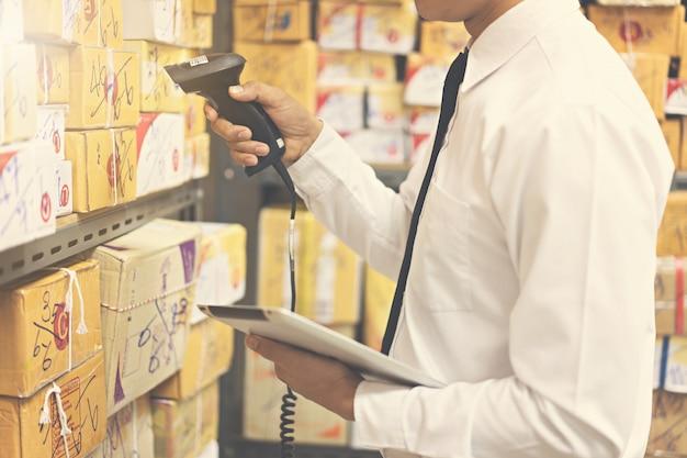 Pracownik kontroli i skanowania pakietu w magazynie. Premium Zdjęcia