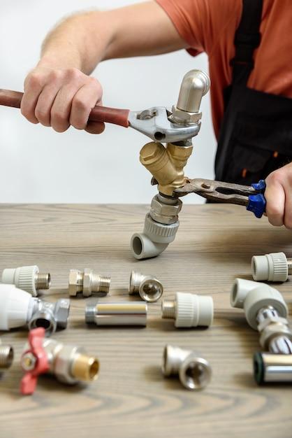Pracownik łączy Elementy Instalacji Hydraulicznej. Premium Zdjęcia