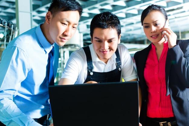 Pracownik lub kierownik produkcji i obsługa klienta, spójrz na laptopa w fabryce tekstylnej i pomóż przez telefon Premium Zdjęcia