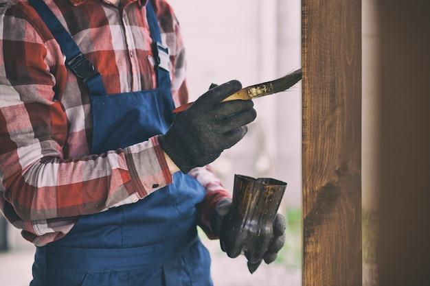 Pracownik Maluje Drewniany Taras Premium Zdjęcia