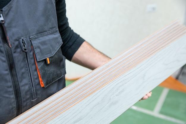 Pracownik Mężczyzna Trzyma Biały Laminat Drewniany Premium Zdjęcia
