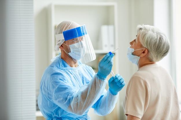 Pracownik Nowoczesnego Laboratorium W Sprzęcie Ochrony Osobistej, Badający Starszą Kobietę Na Koronawirusa Metodą Wymazu Z Nosa Premium Zdjęcia