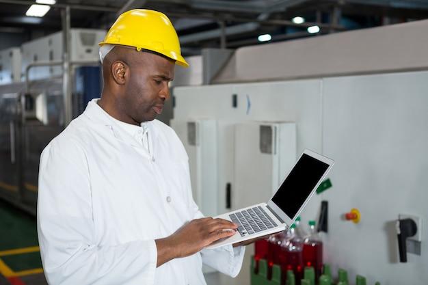 Pracownik Płci Męskiej Za Pomocą Laptopa W Fabryce Soków Darmowe Zdjęcia