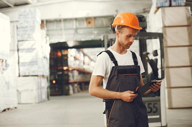 Pracownik Przemysłowy W Fabryce W Pomieszczeniu. Młody Technik Z Pomarańczowym Ciężkim Kapeluszem. Darmowe Zdjęcia