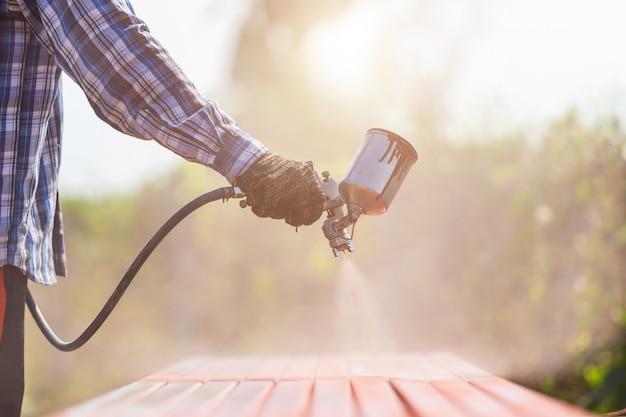 Pracownik rozpylający farbę na stalową rurę, aby zapobiec rdzy na powierzchni Premium Zdjęcia