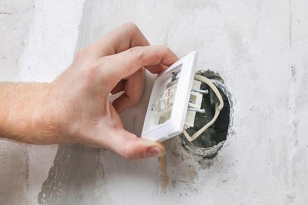 Pracownik Usuwa Włącznik światła Do Tapetowania. Premium Zdjęcia