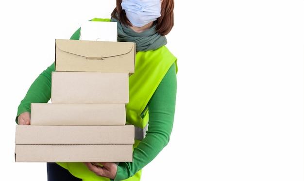 Pracownik W Zielonej Kamizelce Trzyma Dużo Pudełek Papierowych, Koncepcja Dostawy. Premium Zdjęcia