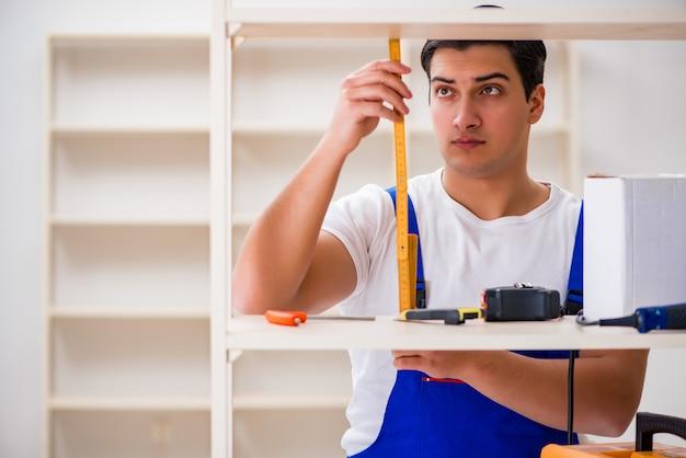 Pracownika mężczyzna naprawia gromadzić półka na książki Premium Zdjęcia