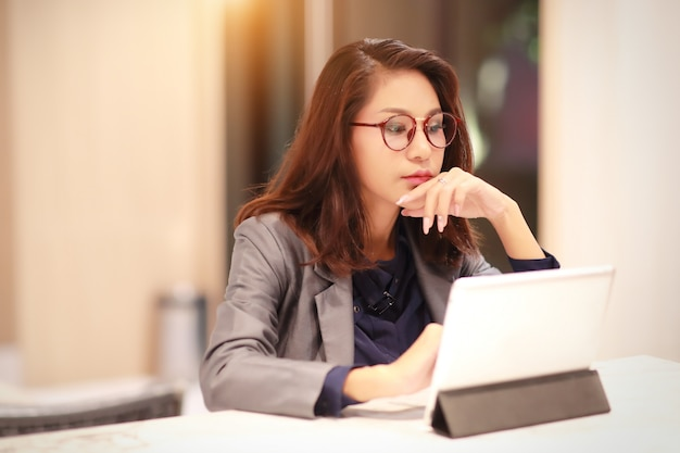 Pracująca i urocza kobieta w okularach za pomocą tabletu (praca w domu) Premium Zdjęcia
