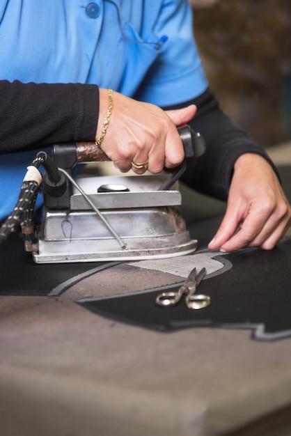 Prasowanie tkaniny przez firmę semstress. żelazko krawcowe w warsztacie krawieckim. Premium Zdjęcia
