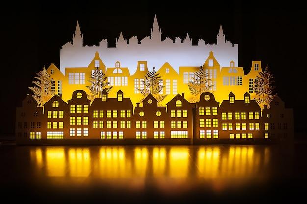 Prawdziwe Paper Art Night Winter Gold Town Z Noworocznymi światłami. Wesołych świąt. Premium Zdjęcia