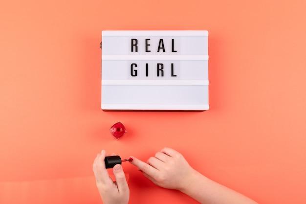 Prawdziwy Tekst Dziewczyny Na Lightbox I Ręce Dziewczyny Maluje Paznokcie Czerwonym Lakierem Do Paznokci Na Tle Koralowców Premium Zdjęcia