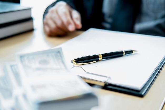 Prawnik biznesmen w garniturze ukrywa pieniądze. łapówka w formie banknotów dolarowych. Premium Zdjęcia