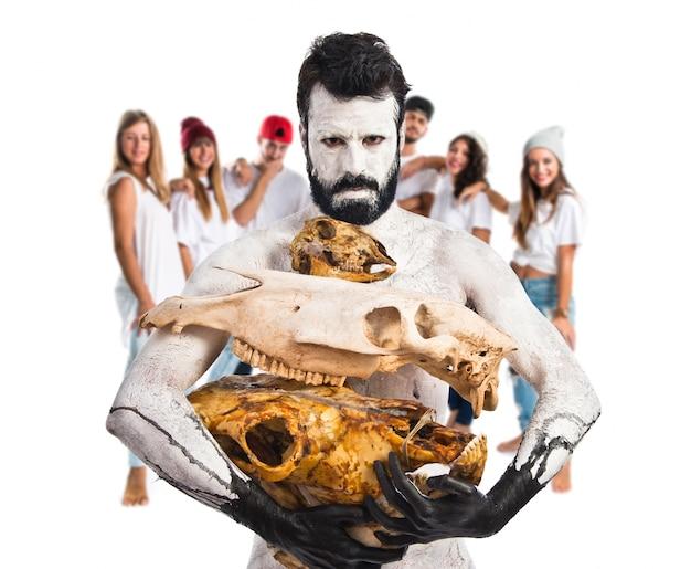 Prehistoryczny Człowiek Trzymający Zwierzę Czaszki Premium Zdjęcia