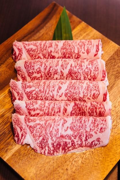 Premium rare plasterki wagyu a5 wołowina z marmurkowatą konsystencją na kwadratowym drewnianym talerzu. Premium Zdjęcia