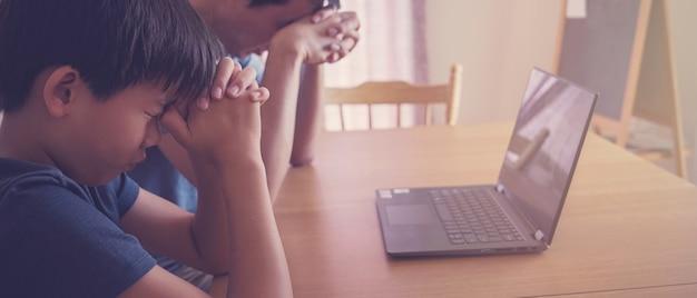Preteen Boy Modlący Się Z Ojcem Rodzicem Z Laptopem, Rodzina I Dzieci Wspólnie Modlą Się Online W Domu Premium Zdjęcia