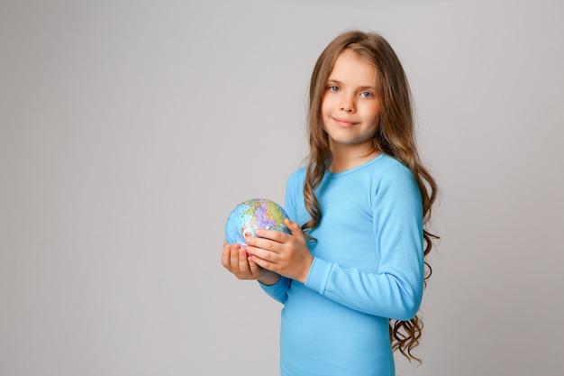 Preteen dziewczyna trzyma ziemską kulę ziemską Premium Zdjęcia