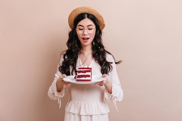 Pretty Chinka W Okularach, Trzymając Talerz Z Deserem. Atrakcyjna Kobieta Azji Kręcone Patrząc Na Ciasto. Darmowe Zdjęcia