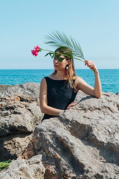 Pretty Woman Gospodarstwa Kwiat I Palma Liści Przechyla Się Na Skale W Pobliżu Morza Darmowe Zdjęcia
