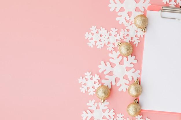 Prezent na boże narodzenie w rękach kobiet i notatnik na różowym tle, widok z góry Premium Zdjęcia