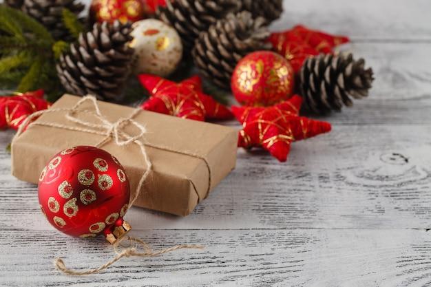 Prezent Na Boże Narodzenie Z Czerwonymi Kulkami łuk Na Biały Drewniany Stół Premium Zdjęcia