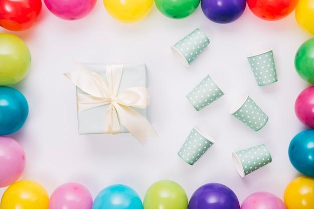 Prezent Urodzinowy I Filiżanka Jednorazowa Wewnątrz Granicy Balony Na Białym Tle Darmowe Zdjęcia