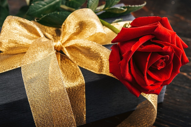 Prezent Zapakowany W Czarny Papier I Złotą Wstążkę. Na Górze Pudełka Znajduje Się Luksusowa Czerwona Róża. Premium Zdjęcia