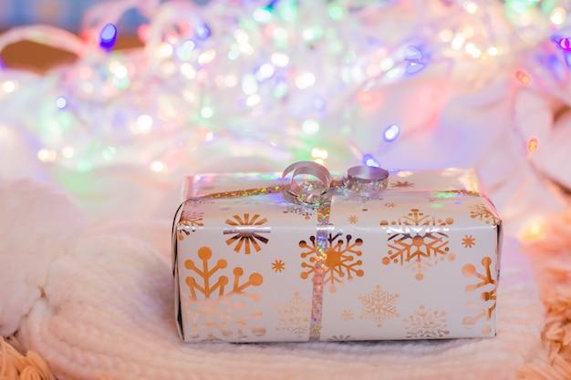 Prezent zapakowany w świąteczne opakowanie związany ze srebrną wstążką na białym dzianym produkcie na tle bokeh różnokolorowych świateł. koncepcja świątecznych przygotowań Premium Zdjęcia