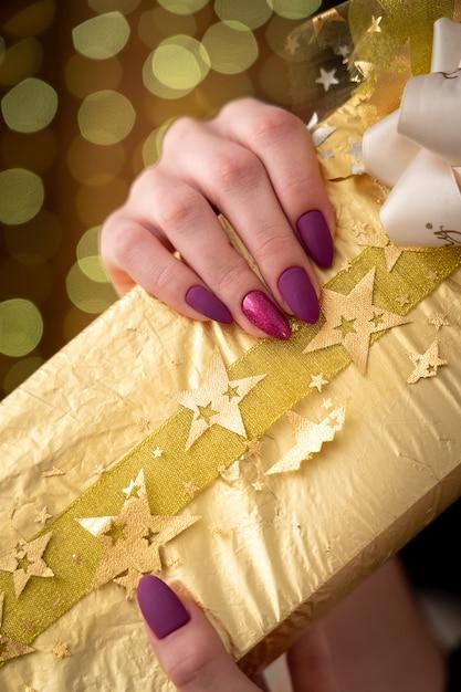 Prezent Zapakowany W Złoty Papier Zabandażowany Wstążką Ozdobiony Kokardą Z Tkaniny Premium Zdjęcia