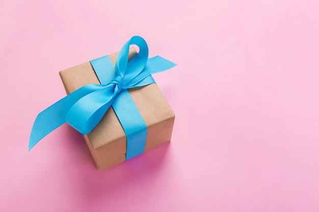 Prezent zawijający i dekorujący z błękitnym łękiem na różowym tle z kopii przestrzenią. płaski układ, widok z góry Premium Zdjęcia