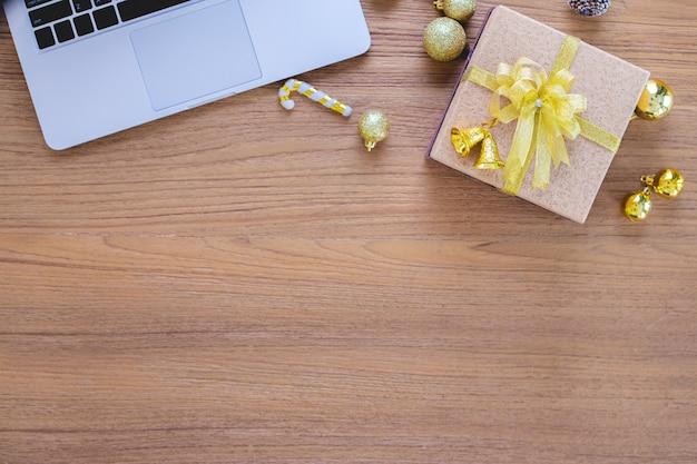 Prezenta pudełko na drewnianym stole i laptopie. Premium Zdjęcia