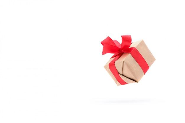 Prezenta pudełko z czerwonym faborkiem odizolowywającym w powietrzu na bielu. Premium Zdjęcia