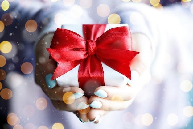 Prezenty Czasu - Pudełko W Dłoni Dziewczynki Ze Złotymi światłami Premium Zdjęcia