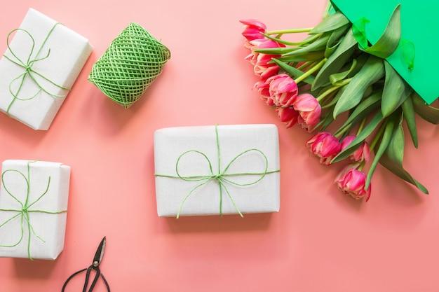 Prezenty I Czerwone Kwiaty Tulipanów W Zielonej Torebce Papierowej Na Różowo. Wiosna. Dzień Matki. Premium Zdjęcia