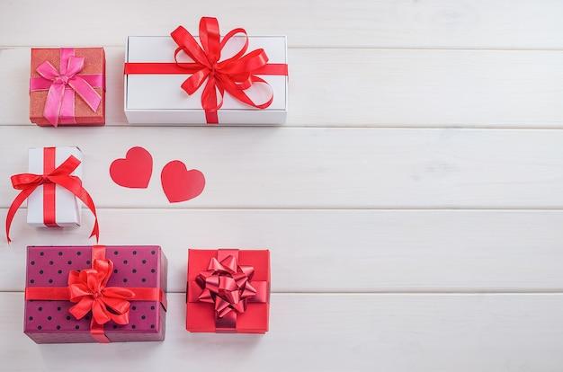Prezenty, Tła Na Walentynki, Dzień Matki. Wielokolorowe Pudełka Na Prezenty Z Czerwonymi Wstążkami I Sercami Na Białym Tle Drewniane Z Miejsca Na Kopię. świąteczna Wyprzedaż, Gratulacje. Premium Zdjęcia