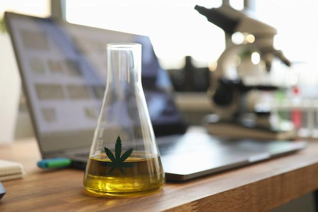 Probówka z żółtym olejem cbd w laboratorium chemicznym Premium Zdjęcia