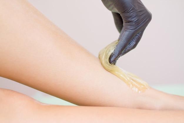 Procedura usuwania włosów na nodze piękna kobieta z pastą cukrową lub miodem woskowym i ręką czarnych rękawiczek Premium Zdjęcia
