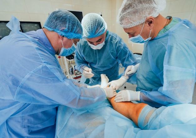Proces Operacji Chirurgii Urazowej. Grupa Chirurgów W Sali Operacyjnej Ze Sprzętem Chirurgicznym. Premium Zdjęcia