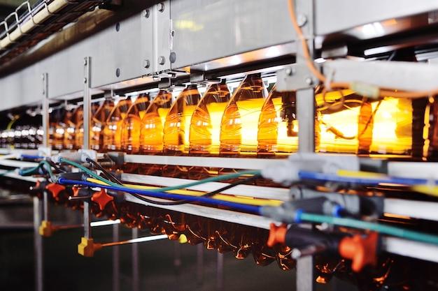 Produkcja Przemysłowa Butelek Plastikowych Do Napojów Niskoalkoholowych, Sody I Oleju Słonecznikowego. Puste Butelki Pet W Kolorze Brązowym Na Tle Nowoczesnego Sprzętu. Premium Zdjęcia