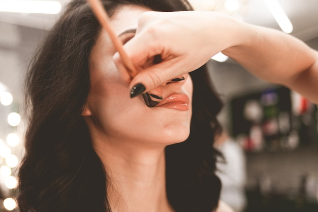 Profesjonalna Visagiste Robi Makijaż Pięknej Kobiecie. Ręka Artysty Makijażu Za Pomocą Pędzla Nakłada Proszek Na Usta Premium Zdjęcia