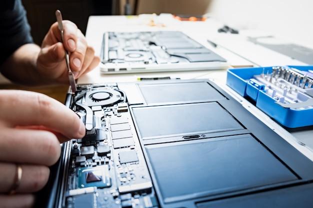 Profesjonalne Sprzątanie Laptopa. Osoba Wykonuje Regularne Czynności Serwisowe I Zmienia Smar Termiczny Nowoczesnych Komputerów Przenośnych, Selektywnie Ustawiając Ostrość Premium Zdjęcia