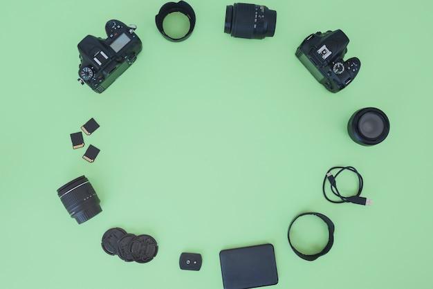 Profesjonalny aparat cyfrowy i akcesoria ułożone na zielonym tle Darmowe Zdjęcia